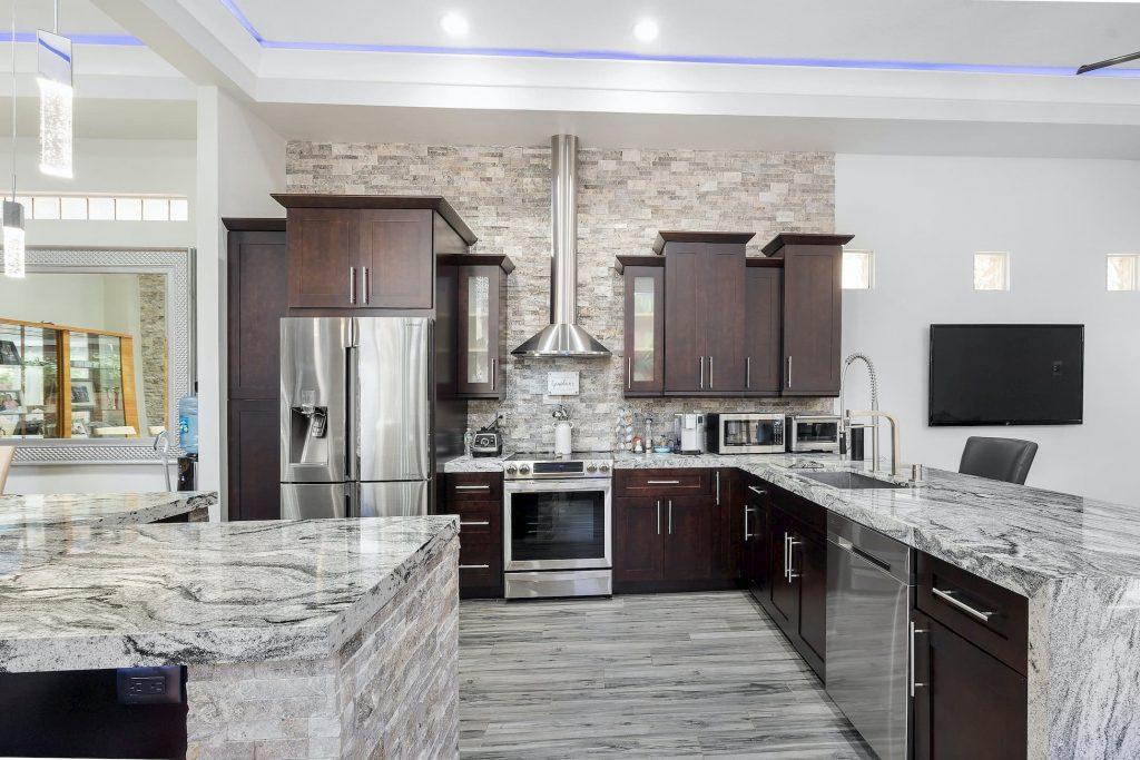 modern kitchen with blue backlit ceiling and tile backsplash wall - kitchen renovations by domot reno group