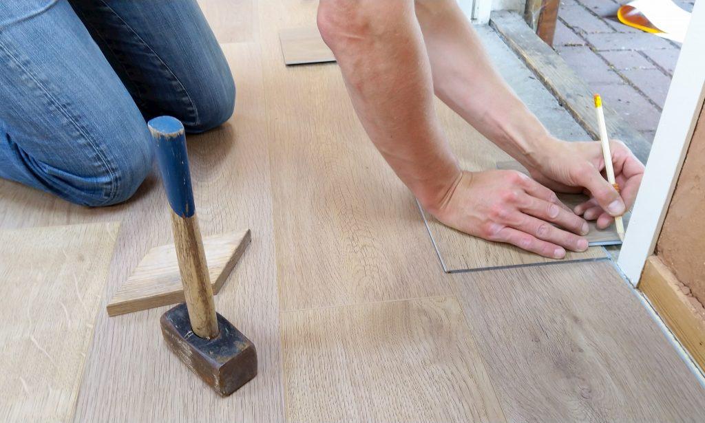 domot reno group team member installing wooden floor - flooring installation