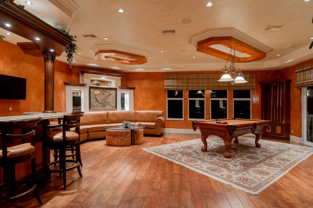 custom family room with crown moudling trim and wooden floor